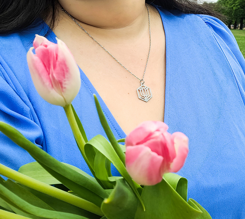 Woman in blue dress wearing stainless steel tulip necklace, holding a bouquet of tulips