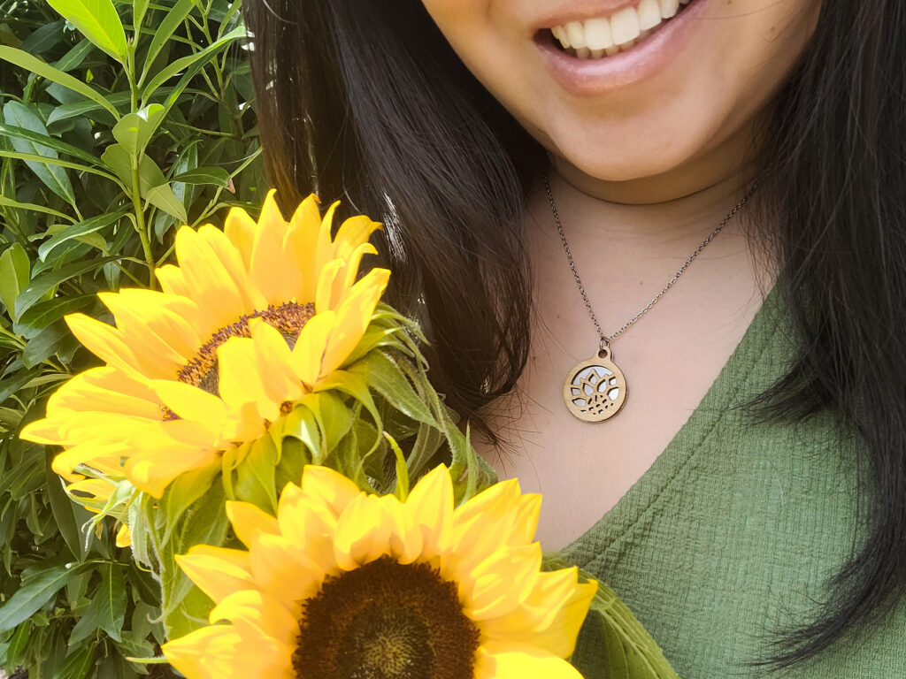 Artist wearing handmade bamboo and stainless steel sunflower necklace and holding sunflowers